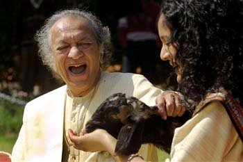 Ravi Shankar, left, and his daughter Anoushka Shankar laugh during the shooting of a film endorsing the strengthening of Indian laws against animal cruelty