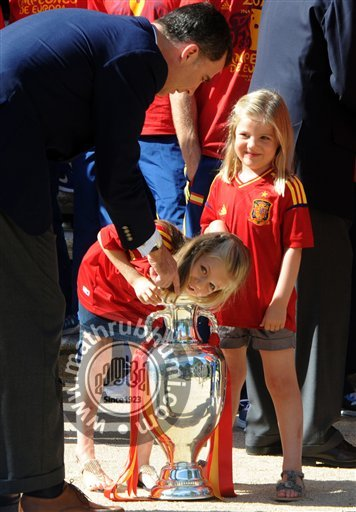 Spain's  Crown Prince Felipe, left points as Spain's Princess Leonor, centre puts her arm into the Euro 2012 trophy next to Princess Sofia right during a visit by the national soccer team members to the Zarzuela Palace in Madrid