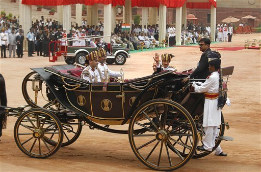 India's new President Pranab Mukherjee, in a traditional horse driven carriage, waves to the media as he arrives at the Presidential Palace, in New Delhi, India, Wednesday, July 25, 2012. Escorted by the President's bodyguards in white-uniforms, Mukherjee, 76, was sworn in Wednesday as India's 13th president in an elaborate ceremony in Parliament. (AP Photo/Manish Swarup)