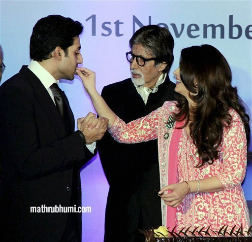 Bollywood actress Aishwarya Rai Bachchan offers cake to her husband actor Abhishek Bachchan as her mega actor Amitabh Bachchan looks on during her birthday celebration in Mumbai on Thursday. Aishwarya was conferred with the French civilian award, Officer Dan Ordre Arts et des Lettres at the function. PTI Photo 