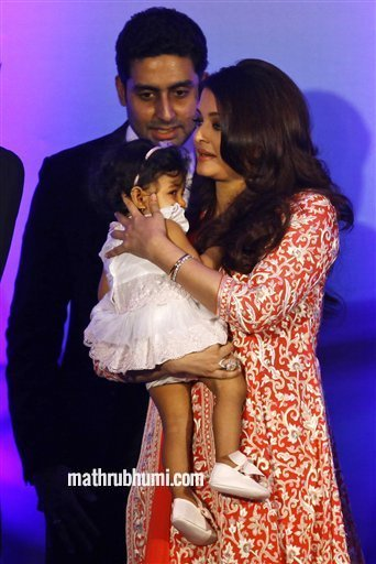 Bollywood actress Aishwarya Rai Bachchan holds her daughter Aaradhya as her husband actor Abhishek Bachan walks with her during a function where she received the second highest French civilian award 'Officer Dan Ordre Arts et des Lettres', in Mumbai, India Thursday, Nov 1, 2012 