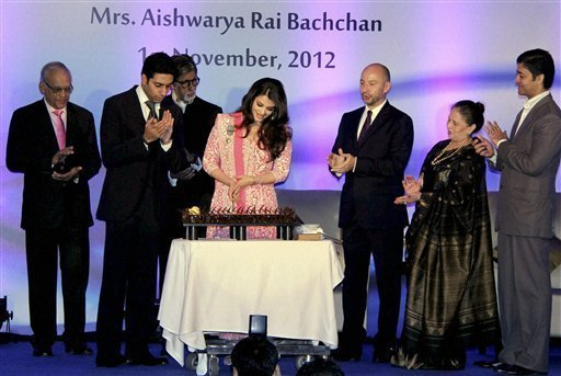 Bollywood actress Aishwarya Rai Bachchan cuts a cake on her birthday as her husband Abhishek Bachchan, father-in-law Amitabh Bachchan and French Ambassador to India, Francois Richier (3rd R) applaud at a function in Mumbai on Thursday. Aishwarya was conferred with the French civilian award, Officer Dan Ordre Arts et des Lettres at the function. PTI Photo 